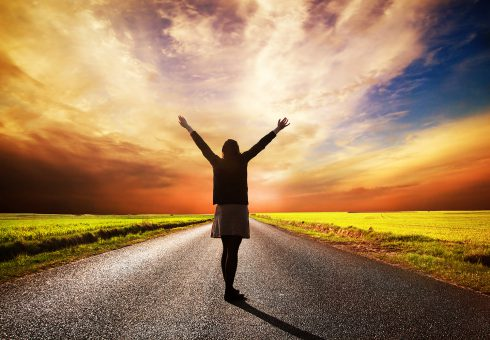 Happy woman standing with hands up on long straight road facing the sun. Sunset sky